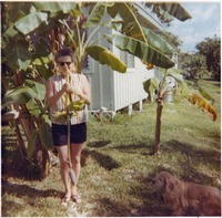 [Cookie Dugger among her banana plants outside of her home]