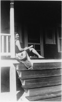Woman Sits On the Stairs Of A Beach House
