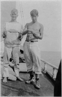 [Two boys stand on the deck of their sailboat and show off two undersized fish around 1920]