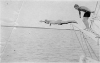 [Two boys dive from the prow of their sailing vessel in Pine Island Sound around 1920]