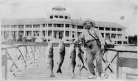 [Fisherman displays his catch at the Tarpon House dock]