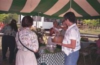 [Tour participants of the Sanibel Historic Village and Museum try produce from the garden]