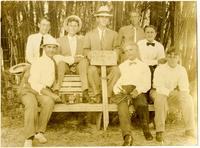 Eight men on a bench holding sign