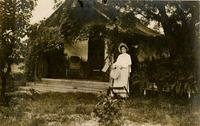 Orline Thatcher Standing in Front of Tent House